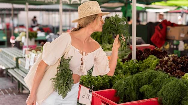 Mulher sentindo o cheiro de endro do mercado Foto gratuita