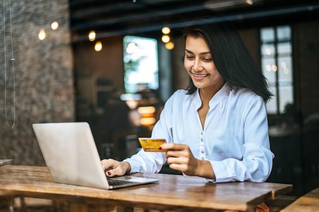 Mulher sentou-se com um laptop e pagou com cartão de crédito em um café Foto gratuita