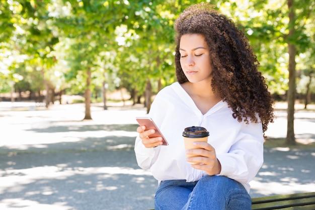 Mulher séria, bebendo café e usando smartphone no banco Foto gratuita
