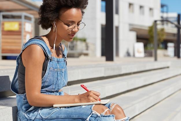 Mulher séria, com pele escura e saudável, concentrada em escrever um ensaio, segura uma caneta, faz anotações no bloco de notas, usa roupas jeans, posa em escadas, ouve um livro de áudio em fones de ouvido, posa em vista da cidade Foto gratuita