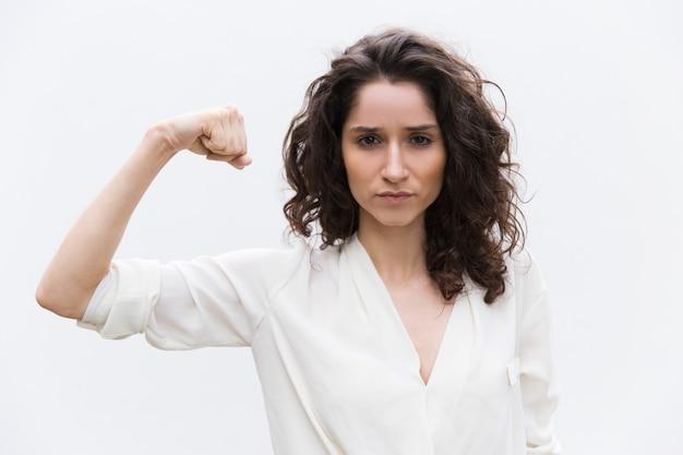 Mulher séria confiável flexionando os bíceps Foto gratuita