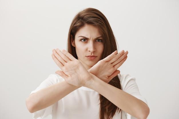 Mulher séria e confiante faz gestos zangados para recusar ou impedir alguém Foto gratuita