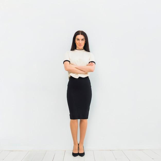 Mulher séria em roupas leves, em pé com os braços cruzados Foto gratuita