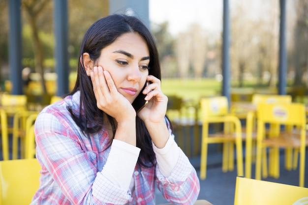 Mulher séria falando no celular no café ao ar livre Foto gratuita