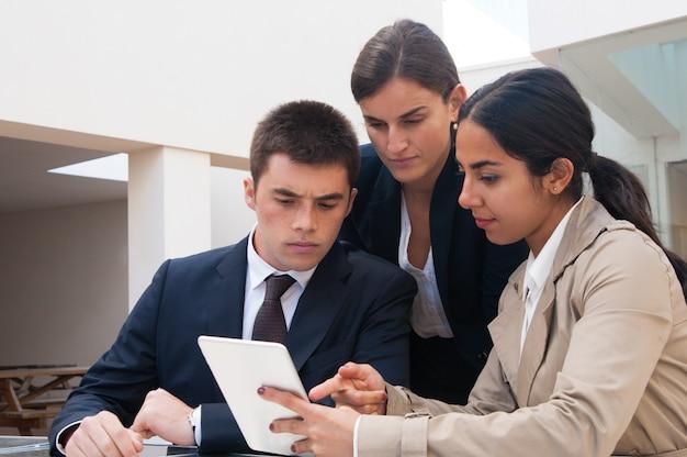 Mulher séria, mostrando a tela do tablet para pessoas de negócios Foto gratuita