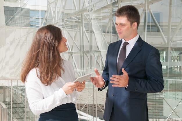 Mulher séria que mostra dados do homem na tabuleta, discutindo o projeto Foto gratuita