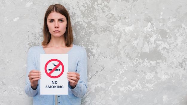Mulher séria segurando com texto não fumar e sinal de pé contra a parede resistiu Foto gratuita