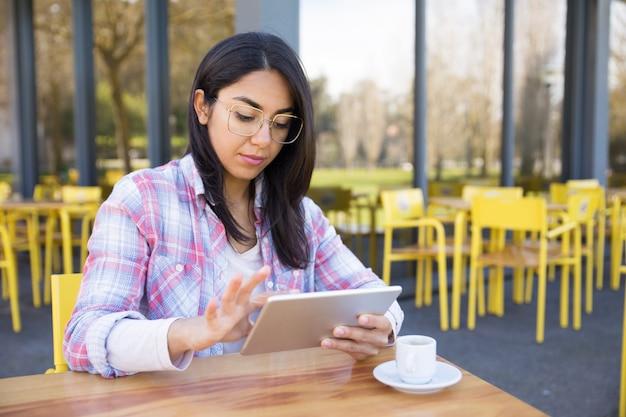 Mulher séria usando tablet e tomando café no café Foto gratuita