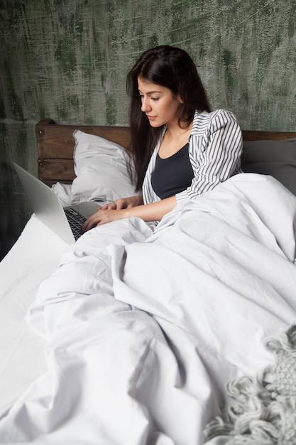 Mulher séria, verificando notícias on-line na cama de manhã Foto gratuita