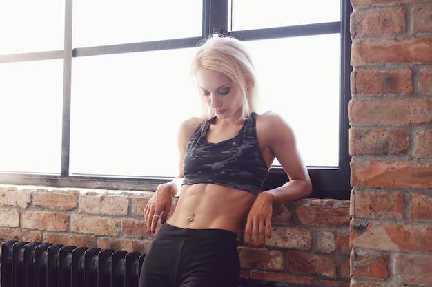 Mulher sexy atleta musculoso posando na janela Foto gratuita