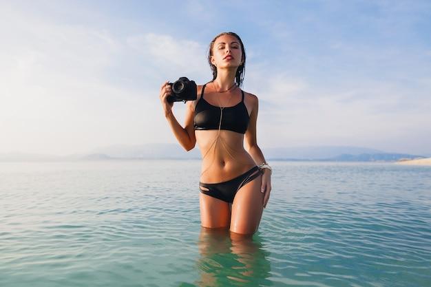 Mulher sexy bonita, corpo esguio perfeito, pele bronzeada, maiô de biquíni preto, em pé na água azul, segurando uma câmera fotográfica digital, calor, férias de verão tropical, tendência da moda, cintura, barriga, quadris Foto gratuita