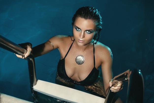 Mulher sexy na piscina à noite Foto Premium