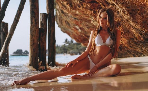 Mulher sexy no desgaste da nadada que encontra-se pelo oceano sob as cavernas Foto gratuita