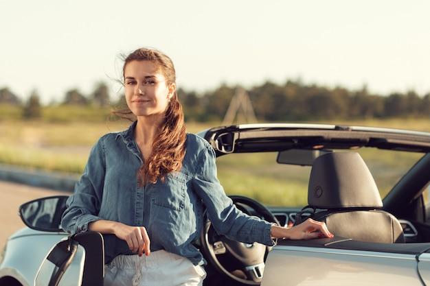 Mulher sexy, posando ao lado do carro cabrio Foto Premium