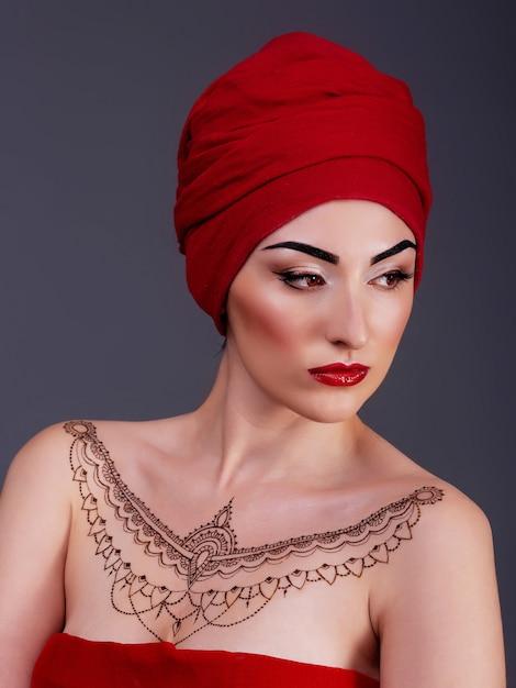 Mulher sexy, posando no estúdio, lábios vermelhos, fundo azul violeta isolado, tatuagem de hena no peito Foto Premium