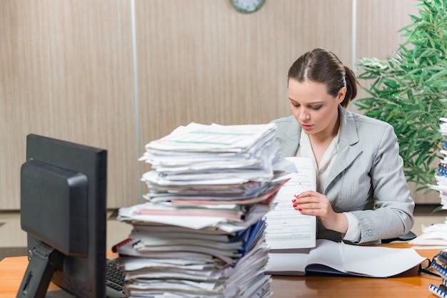 Mulher sob estresse do trabalho excessivo de papel Foto Premium