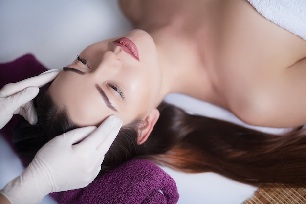 Mulher sob massagem facial profissional no spa de beleza Foto Premium