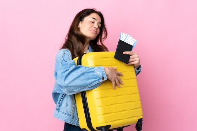 Mulher sobre azul isolado em férias com mala e passaporte Foto Premium