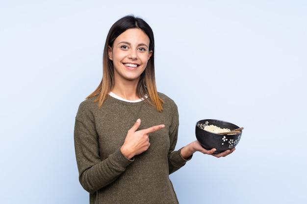 Mulher sobre parede azul e apontando-o enquanto segura uma tigela de macarrão com pauzinhos Foto Premium