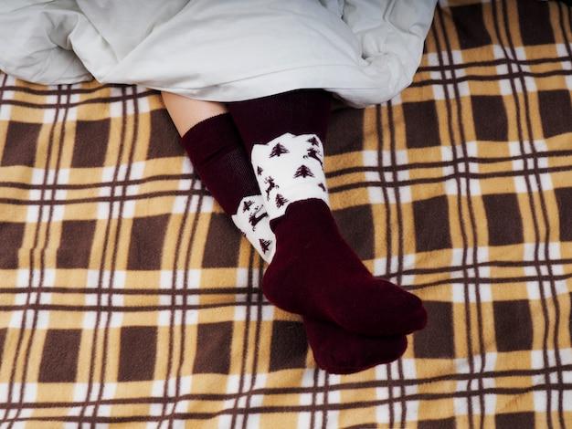 Mulher sofá-cama resto xadrez estilo de vida tonificado macio, pés com meias, manta marrom Foto Premium