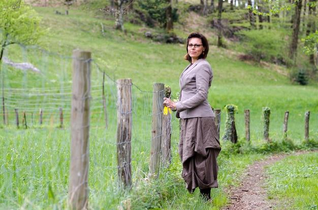 Mulher solitária caminhando em um parque com uma cerca de madeira Foto gratuita