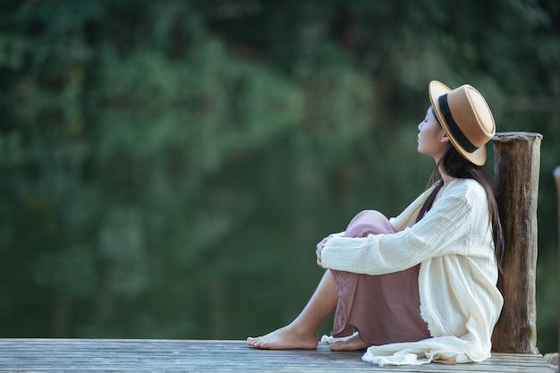 Mulher solitária sentado na jangada à beira-mar Foto gratuita