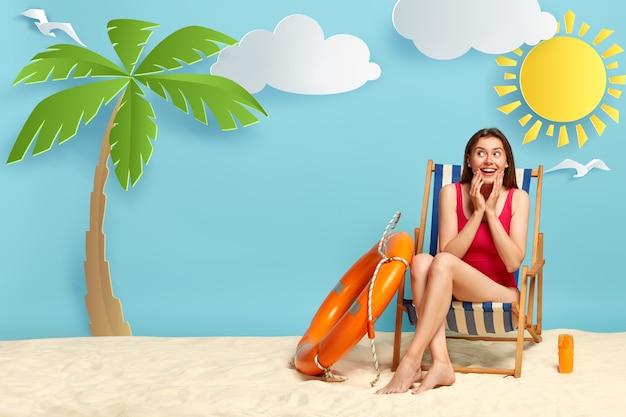 Mulher sonhadora positiva gosta de dia quente na costa, senta-se na espreguiçadeira, usa biquíni vermelho, usa protetor solar para proteger a pele do sol Foto gratuita