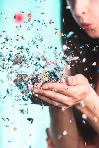 Mulher soprando confete das mãos dela Foto gratuita