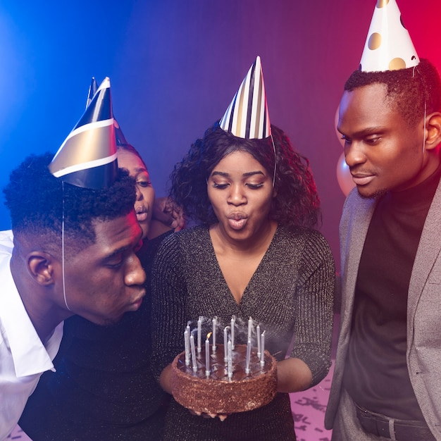Mulher soprando velas em seu bolo de feliz aniversário Foto gratuita
