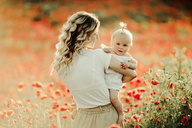 Mulher sorri para um bebê entre campo de flores Foto gratuita
