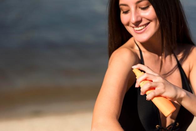 Mulher sorridente a aplicar protetor solar na praia Foto gratuita
