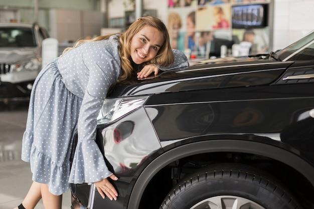 Mulher sorridente, abraçando o carro moderno Foto gratuita