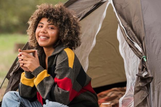 Mulher sorridente acampando ao ar livre com tenda Foto gratuita
