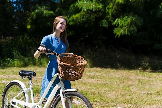 Mulher sorridente andando ao lado de sua bicicleta Foto gratuita