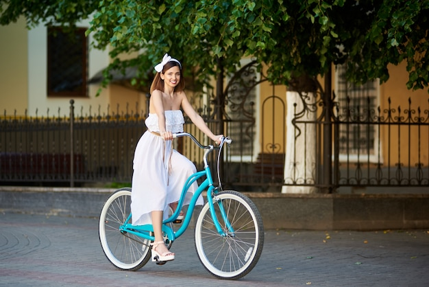 Mulher sorridente, andar de bicicleta em uma rua ensolarada da cidade Foto Premium
