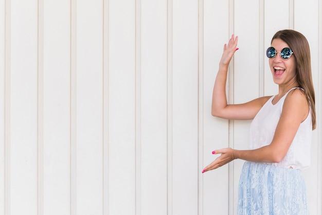 Mulher sorridente animada, apontando pelas mãos no espaço vazio Foto gratuita