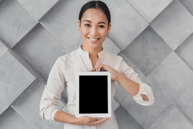 Mulher sorridente, apresentando modelo de tablet Foto gratuita