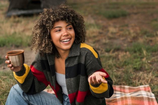 Mulher sorridente aproveitando o tempo ao ar livre enquanto acampa Foto Premium