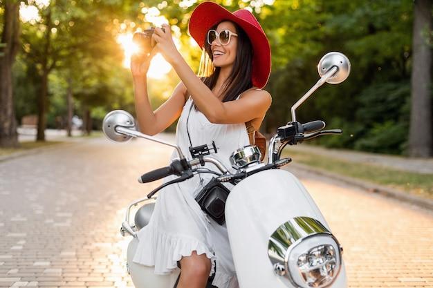 Mulher sorridente atraente andando de moto na rua com roupa estilo verão, vestido branco e chapéu vermelho, viajando de férias, tirando fotos na câmera fotográfica vintage Foto gratuita