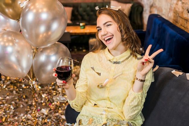 Mulher sorridente atraente desfrutando de festa segurando o copo de vinho Foto gratuita