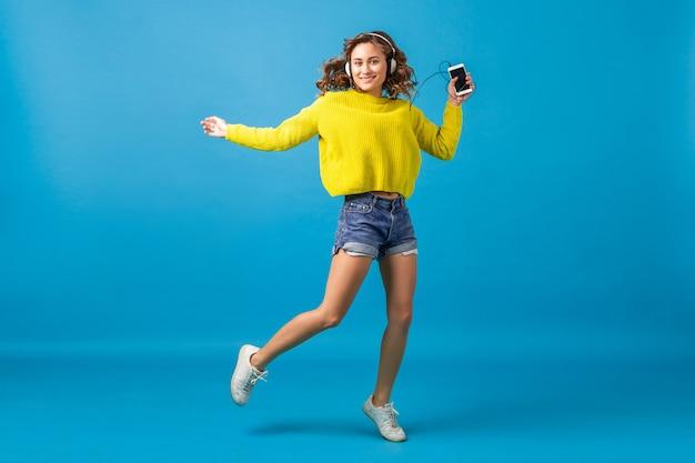 Mulher sorridente atraente feliz pulando dançando ouvindo música em fones de ouvido em roupa hipster isolada no fundo azul do estúdio, vestindo shorts e suéter amarelo Foto gratuita