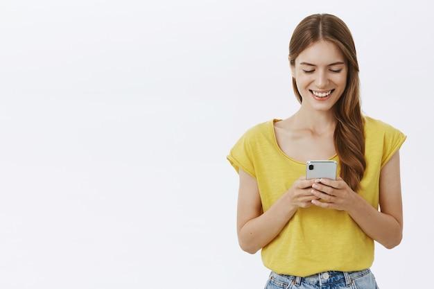 Mulher sorridente atraente usando telefone celular, mensagem de texto no aplicativo ou rede social Foto gratuita