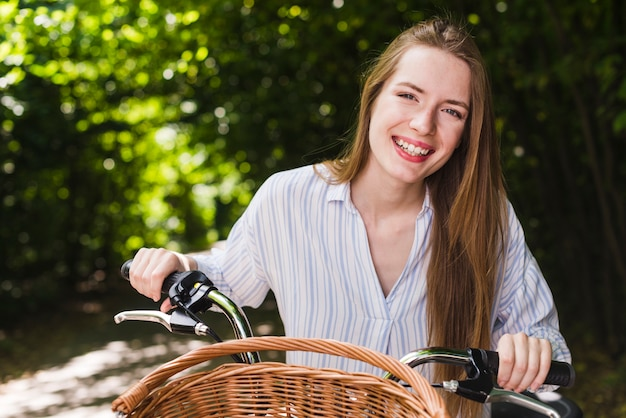Mulher sorridente, bicicleta Foto gratuita