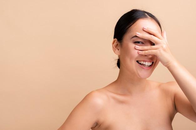 Mulher sorridente close-up, cobrindo os olhos com cópia-espaço Foto gratuita