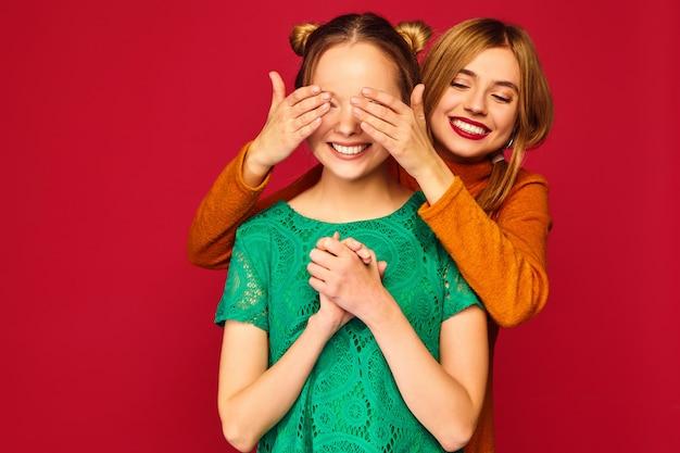 Mulher sorridente, cobrindo os olhos com as mãos para a amiga Foto gratuita