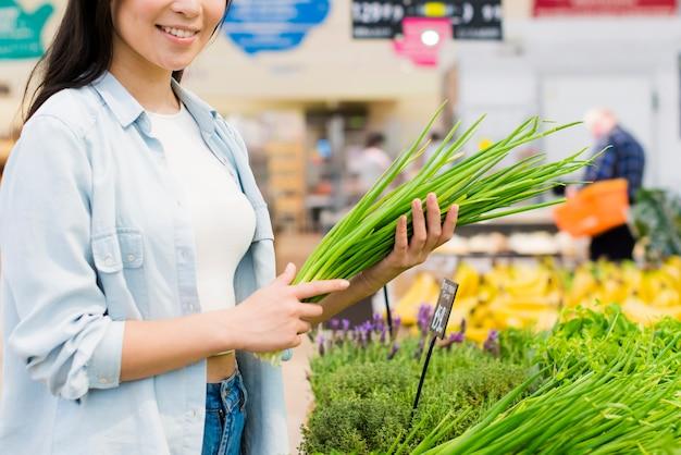 Mulher sorridente, colheita, horticultura, em, mercearia Foto gratuita