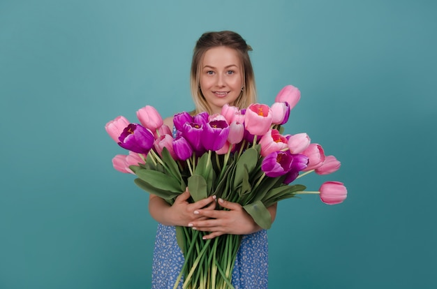 Mulher sorridente com buquê de tulipas cor de rosa e roxas. conceito de verão e primavera. Foto Premium