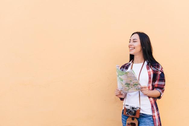 Mulher sorridente, com, câmera, ao redor, dela, pescoço, segurando, mapa Foto gratuita