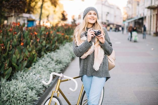 Mulher sorridente com câmera e bicicleta Foto gratuita