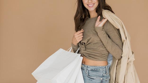 Mulher sorridente com casaco no ombro e sacolas de compras Foto gratuita